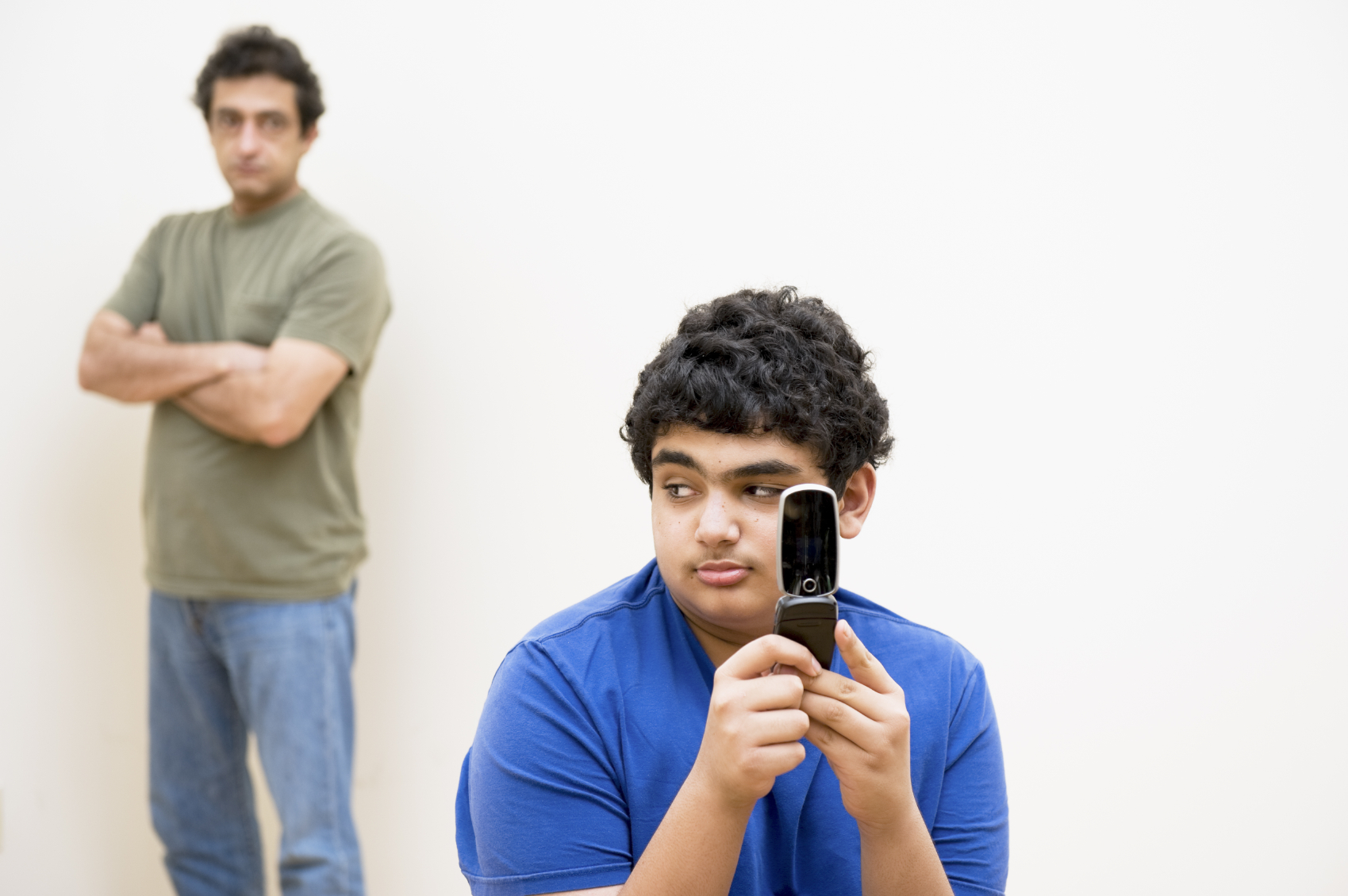 teen_texting_dad_in_background
