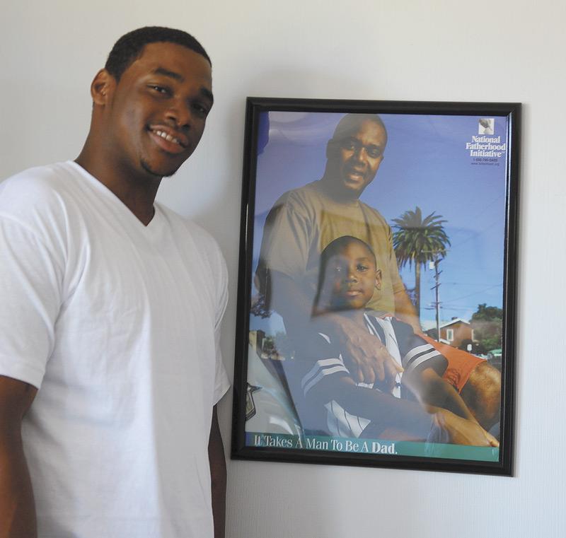 Kyle Parrish stands next to NFI's fatherhood poster.